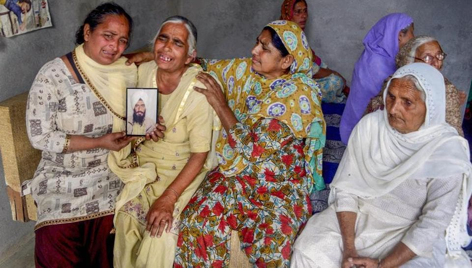Family members of one of the 39 Indian workers killed in Iraq mourn holding his portrait, on the outskirts of Amritsar on Tuesday.