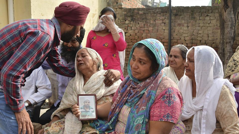 Family members grieve by a portrait of Harsimran Singh, one of the 39 Indian  workers