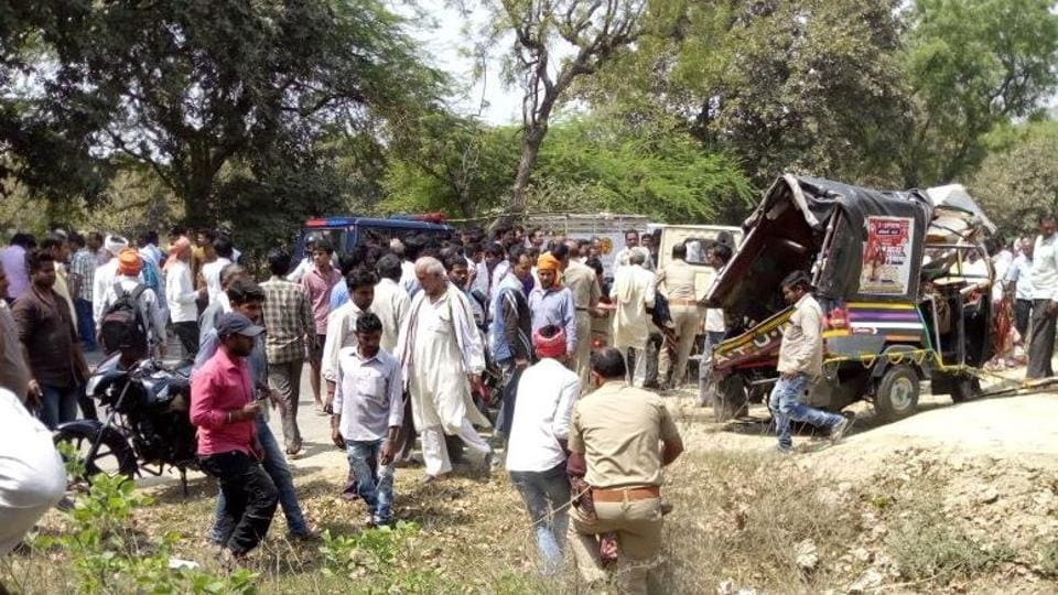 Police and local residents carry an injured at the accident site in Pratapgarh district in Uttar Pradesh.