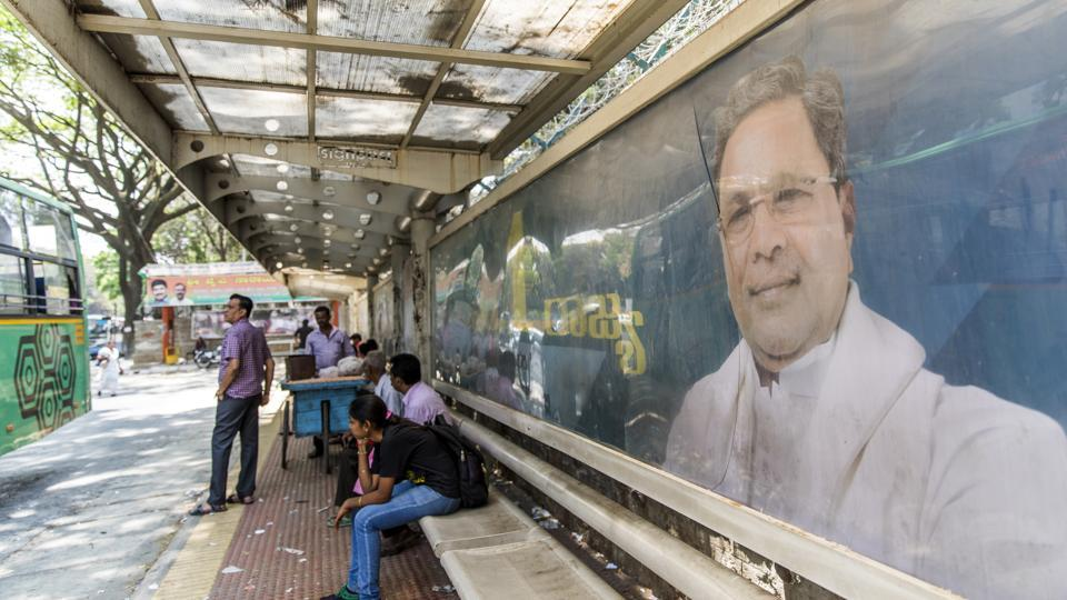 "An election campaign billboard featuring an image of Karnataka Chief Minister K. Siddaramaiah, of the Indian National Congress party (INC), is displayed at a bus stop in Bengaluru, Karnataka. Siddaramaiah had tweeted, ""The Karnataka BJP is so spineless that instead of asking the Centre to waive farmers' loans it is giving accountancy lessons on Twitter.""  (Prashanth Vishwanathan / Bloomberg)"