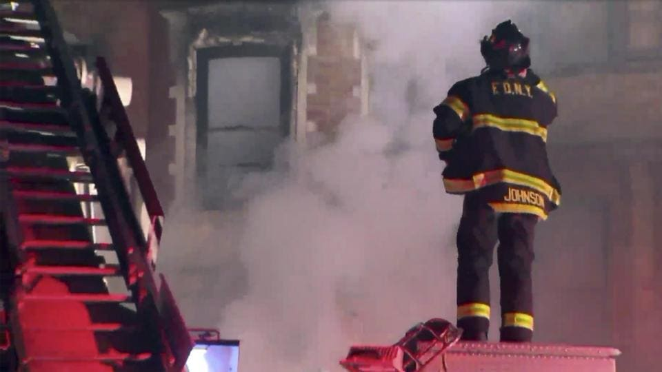New York Firefighters at the scene of a raging fire at an unoccupied residential building being used as a film set in the Harlem section of New York on Thursday.