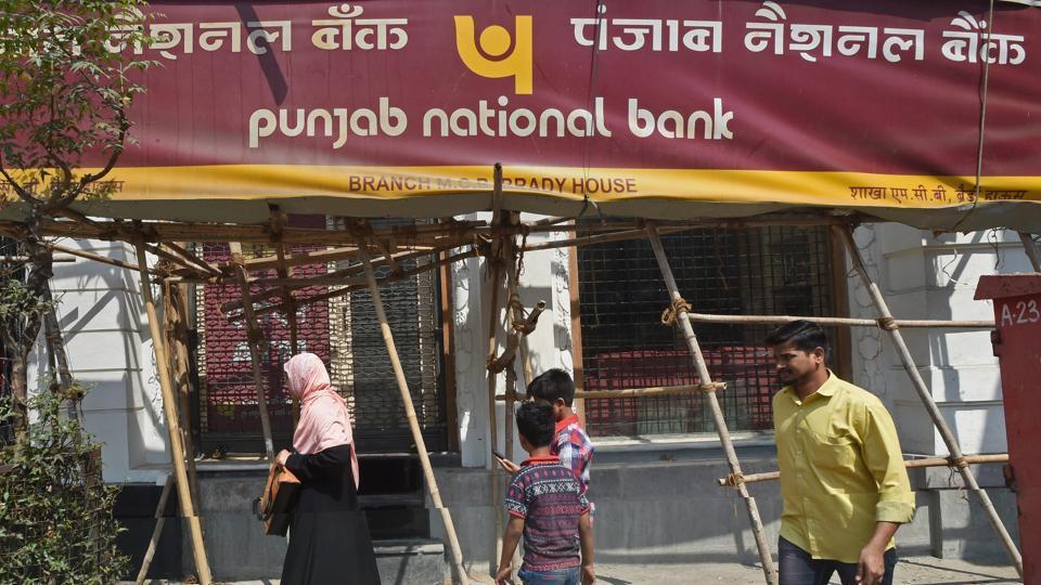People walk past as a CBI team seals the Punjab National Bank's South Mumbai branch at Brady House in Mumbai.