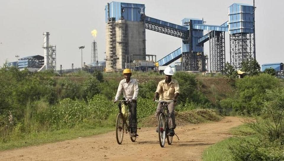 Men ride their bicycles in front of the Bhushan Steel plant in Odisha August 18, 2014.