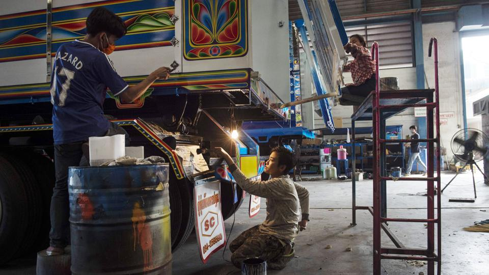 "At a warehouse near Bangkok, dozens of workers cut stickers and spray on designs ranging from traditional flower patterns to Japanese robot anime craze Gundam. It belongs to Sirintra Phichitphajongkit, managing director of Soonchai Industry, one of Thailand's largest truck assemblers that has recently devoted a section to painting trucks. ""I think it's about psychology"" Sirintra told AFP. (Lillian Suwanrumpha / AFP)"