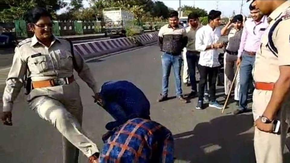 A woman constable kicks a youngster while he does push ups on the road in Neemuch. Police accused the youngster and his friends of harassing college girls.