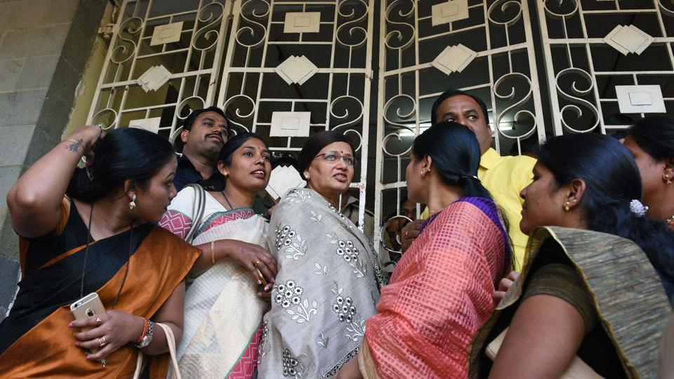 Mayor Mukta Tilak along with corporators stand outside the PMC building gate before a  general body meeting  on Friday. The day was marked by multiple protests by political parties against the new proposed parking policy. All the gates of the building were closed and no one was allowed to go in or come out for some time due to the protests.  (Pratham Gokhale/HT Photo)