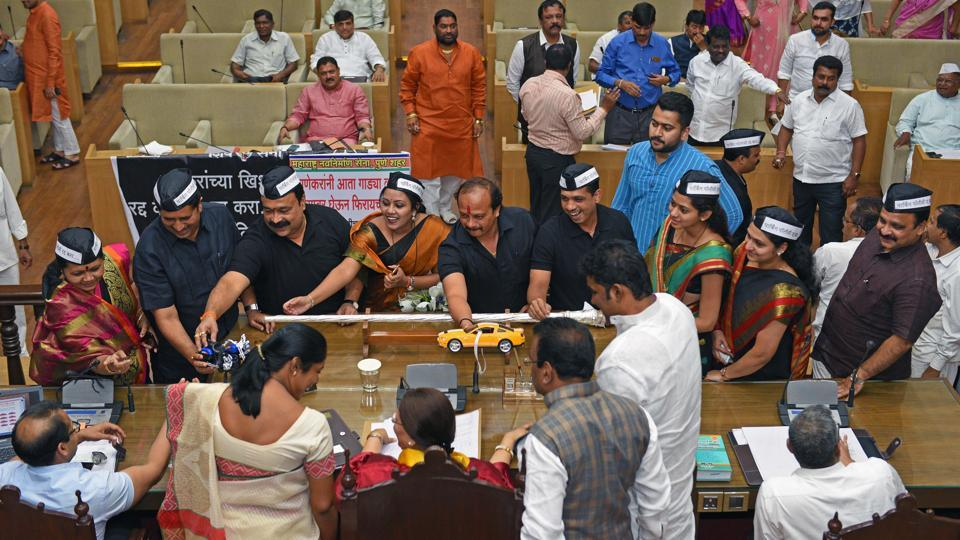 Corporators give toy cars to the mayor and commissioner during a general body meeting to protest against the new proposed parking policy.  (Pratham Gokhale/HT Photo)