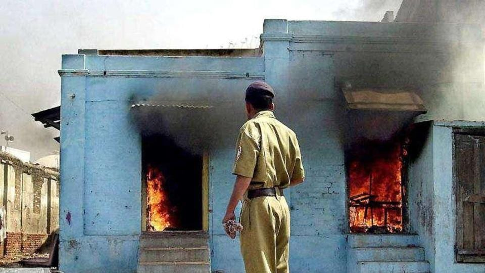 In this photograph taken on February 28, 2002, a policeman looks as fire rages in shops in Ahmedabad following an attack by a mob.