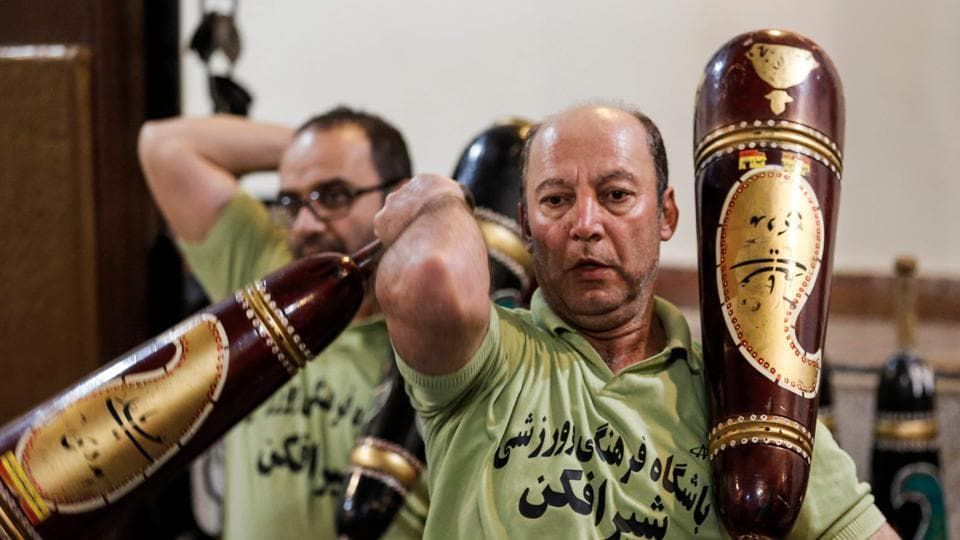 Iranians train with wooden clubs called