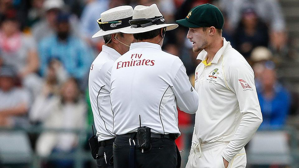 Australian fielder Cameron Bancroft (R) is questioned by umpires Richard Illingworth (L) and Nigel Llong (C) during the third day of the third Test against South Africa at Newlands.
