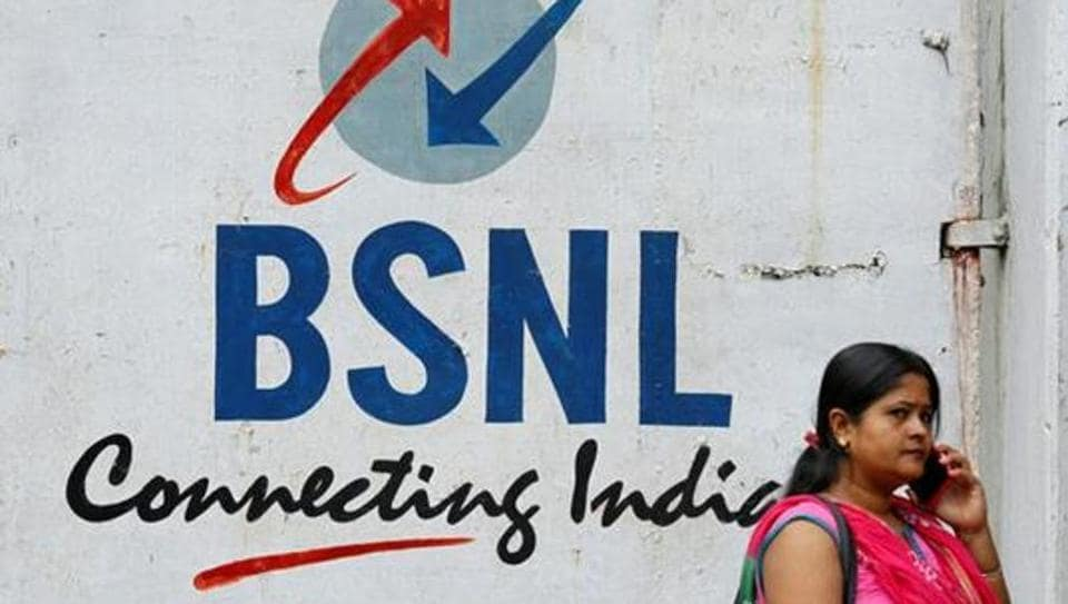 A woman speaks on her mobile phone in front of the logo of Bharat Sanchar Nigam Ltd (BSNL) painted on a wall outside its office in Kolkata, August 24, 2017.