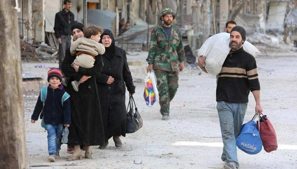 Syrian people walk down a street past a destroyed building as civilians and rebels prepare to evacuate the town of Ain Tarma in the eastern Ghouta region on the outskirts of the capital Damascus, on March 25, 2018.