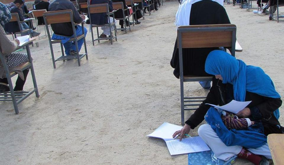 Photo, obtained from the Facebook account of Afghan professor Yahya Erfan and taken on March 16, shows Afghan student Jahantab Ahmadi (bottom right) sitting on the ground with her baby on her lap as she takes an entrance exam for Nasir Khusraw private university, in the central city of Nili, the provincial capital of Daykundi province.