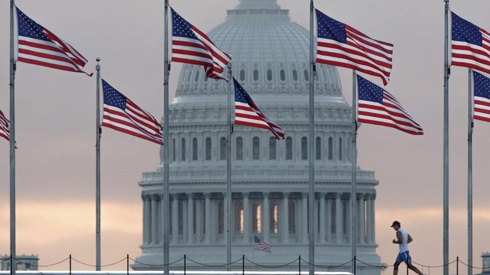 An early morning runner crosses in front of the US Capitol as he passes the flags circling the Washington Monument in Washington.