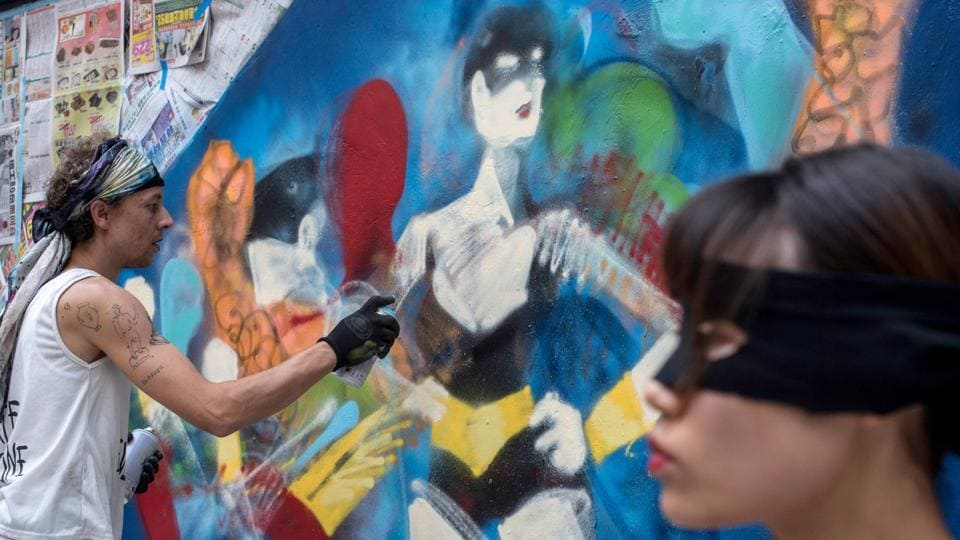 Australian artist Anthony Lister spray paints a portrait of a woman onto a wall in Hong Kong. From murals made famous by Instagram to painting battles, Hong Kong's once largely underground street art scene has exploded in recent years, and is now blossoming across the city's walls and alleyways. (Philip Fong / AFP)