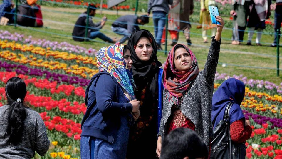 Visitors take selfies on their visit to Indira Gandhi Memorial Tulip Garden, believed to be Asia's largest, in Srinagar on Sunday.