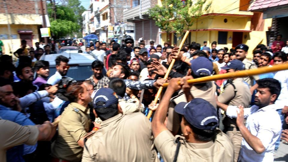 Police control the members of two communities, who clashed in Dehradun on Monday.