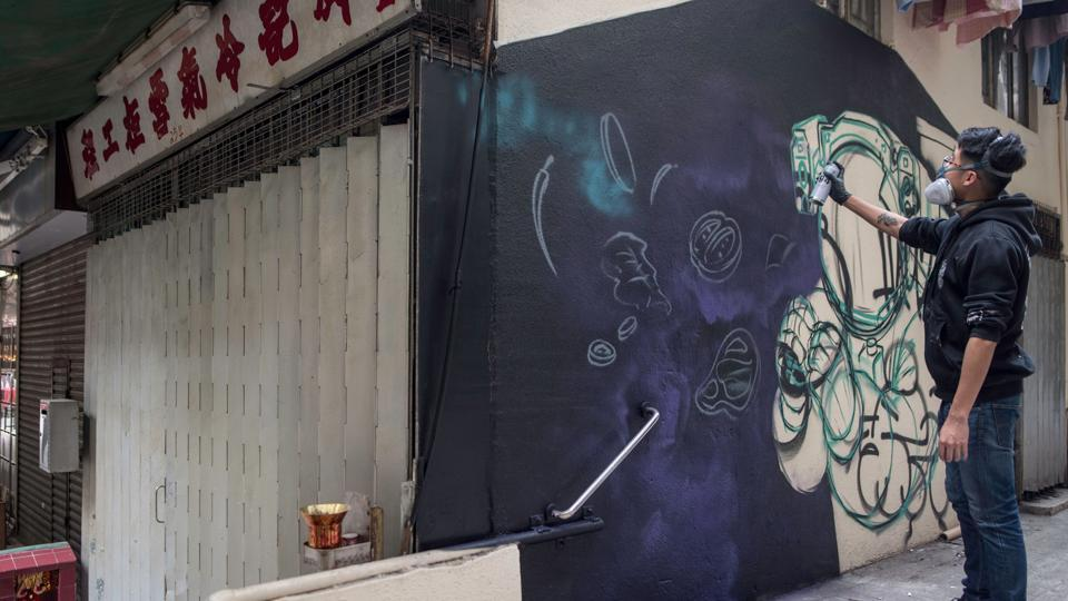 Chinese artist SIK spray paints a mural in the alley of Sai Ying Pun district of Hong Kong. Despite challenges from authorities, street art has enjoyed a boost from growing demand in Asia and an increasing number of exhibitions in recent years, giving it a higher profile and more commercial spin in the city. (Philip Fong / AFP)