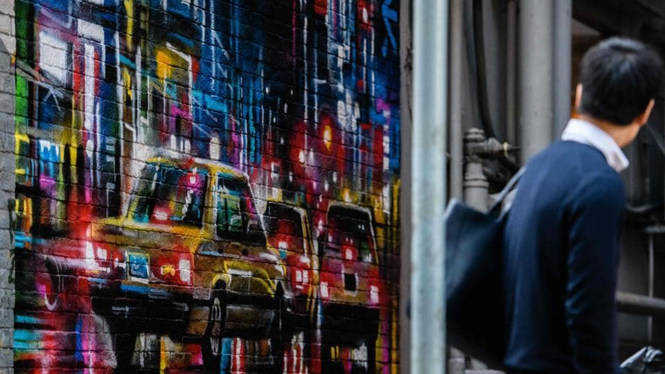 A pedestrian looks at a mural by British artist Dan Kitchener. In 2015, a mosaic of 1970s American cartoon character Hong Kong Phooey by French artist Invader sold at auction in Hong Kong for HK$2 million ($258,000). The popular piece of street art had been destroyed by the city's authorities, infuriating residents, and was later recreated for sale. (Anthony Wallace / AFP)