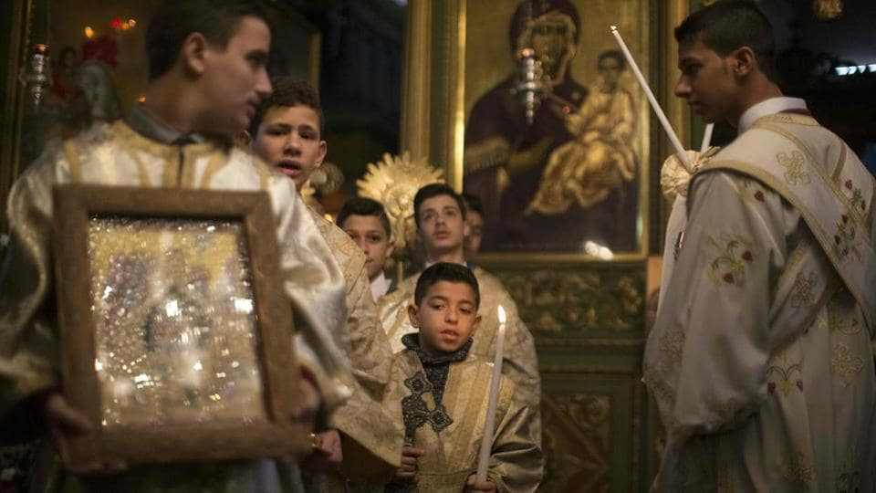 Palestinian Orthodox Christian altar boys attend a Christmas mass at the Saint Porphyrios Greek Orthodox church in Gaza City on January 7, 2017.