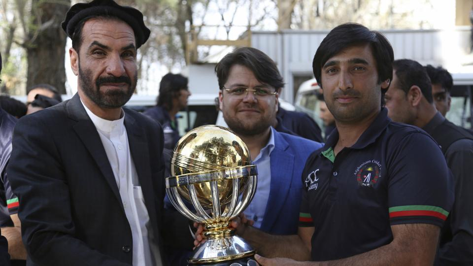 Afghanistan cricket team captain Asghar Stanikzai, right, holds the trophy they won after defeating West Indies in the final of the 2019 ICCWorld Cup qualification tournament.