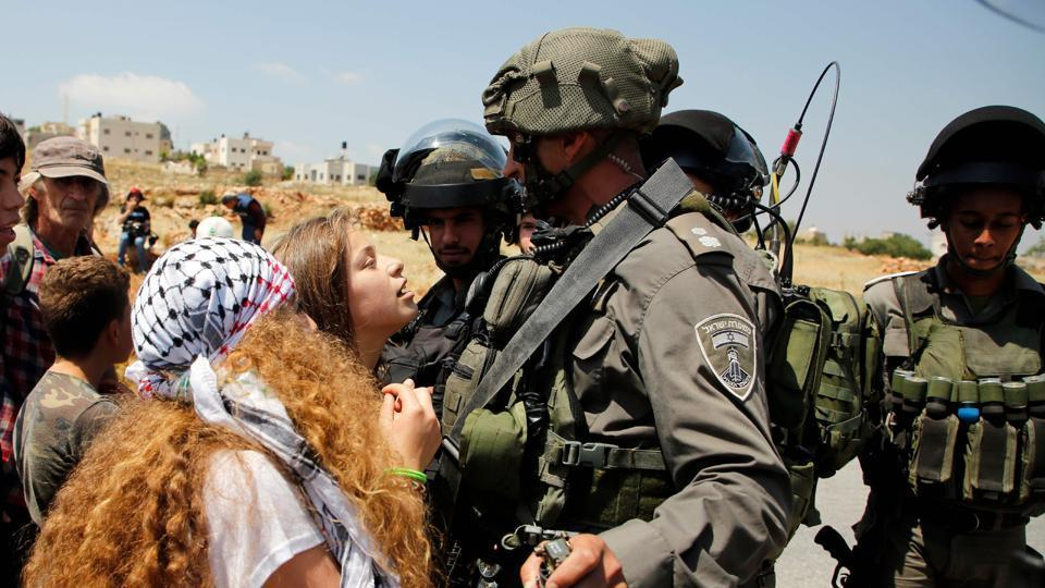 (FILES) This file photo taken on May 12, 2017 shows 17-year-old Ahed Tamimi (C) protesting before Israeli forces in the West Bank village of Nabi Saleh, north of Ramallah, on May 12, 2017.