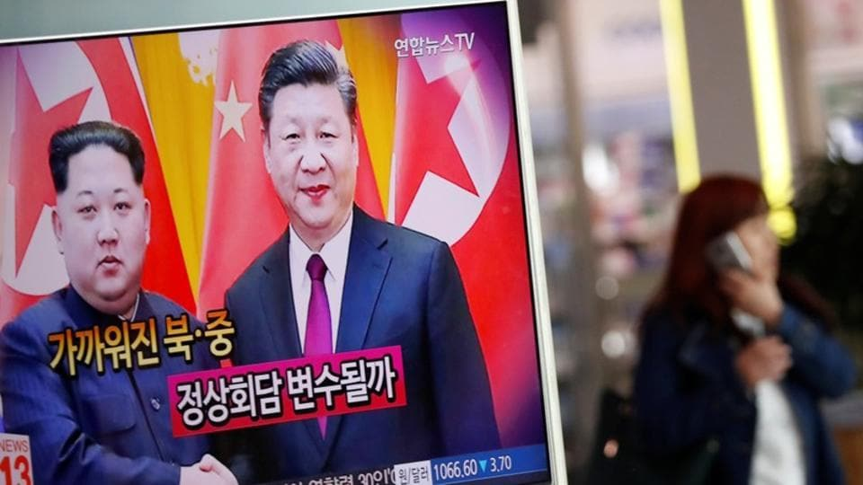 A woman walks past a TV broadcasting a news report on a meeting between North Korean leader Kim Jong Un and Chinese President Xi Jinping in Beijing, in Seoul, South Korea.