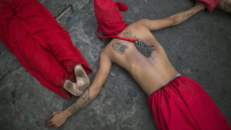 A penitent, with a tattoo of Jesus Christ and his whip resting on his back, lies with other flagellants on a pavement in Mandaluyong City, Philippines. Despite Catholic Church officials discouraging the tradition, Filipinos still practice self-flagellation on Maundy Thursday as a way to atone for sins and commemorate the suffering of Jesus Christ. (AP)