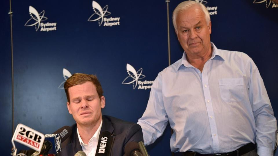 Steve Smith (L) is comforted by his father Peter as he reacts at a press conference at the Sydney Airport. (AFP)