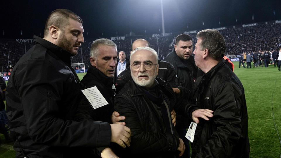 PAOK's Greek-Russian president Ivan Savvidis (C) was escorted out after taking to the pitch carrying a handgun in his waistband during a Greek Superleague match.