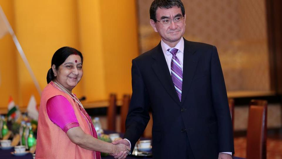 Japan's Foreign Minister Taro Kono (R) shakes hands with his Indian counterpart Sushma Swaraj during their meeting in Tokyo on March 29, 2018.