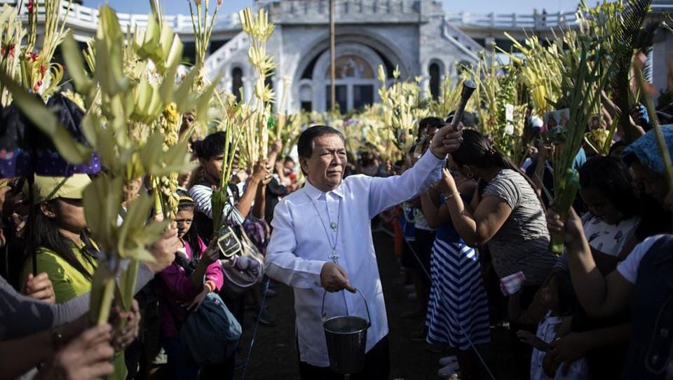 A layman of the Roman Catholic Church blesses palm leaves during Palm Sunday celebrations at the Our Lady of Lourdes Grotto church in Bulacan, north of Manila. Palm Sunday marks the sixth and last Sunday of the Christian holy month of Lent and the beginning of Holy Week with the entrance of Jesus into Jerusalem. (Noel Celis / AFP)