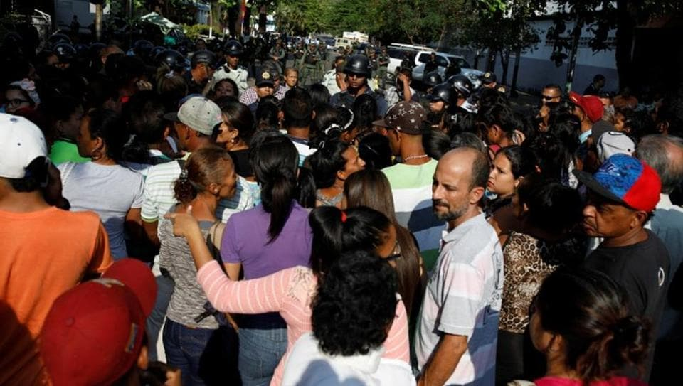 Relatives of inmates at the General Command of the Carabobo Police wait outside the prison in Valencia, Venezuela, on March 28, 2018.