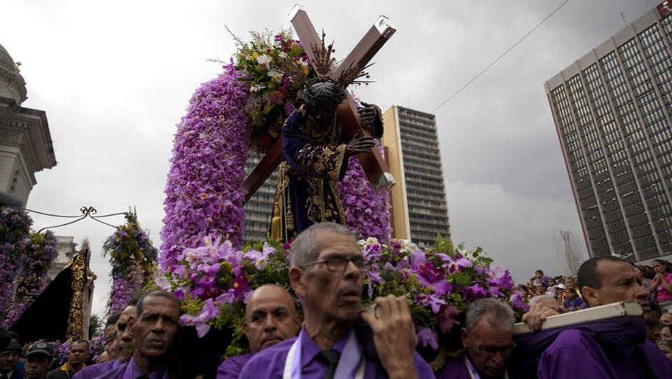"Devotees carry the ""Nazareno de San Pablo"" during a Holy Week procession outside Santa Teresa Cathedral in Caracas, Venezuela, Wednesday, March 28, 2018. The Nazareno de San Pablo is a sculpture from the 17th century. (Ariana Cubillos / AP)"
