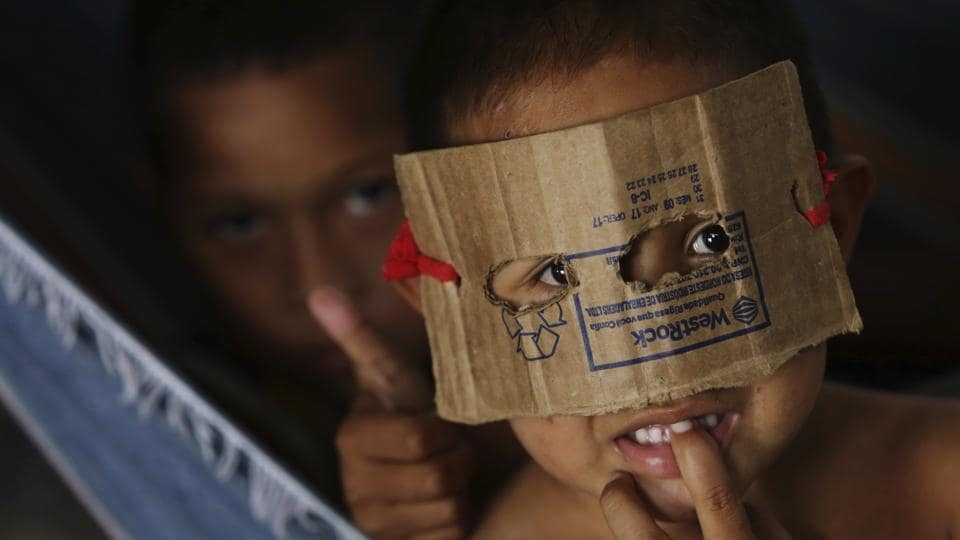 A Warao boy from Venezuela dons a mask fashioned from cardboard at a a shelter in Pacaraima, the main entry point for Venezuelans in the Brazilian state of Roraima. (Eraldo Peres / AP)