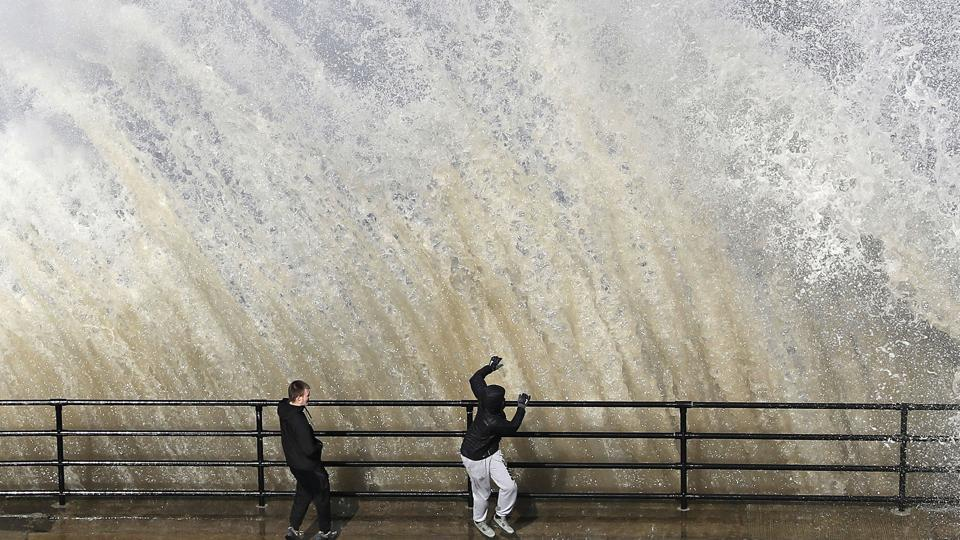 Young men stand by as a giant wave crashes, near Cullercoats on the North East Coast of England,  as the weather takes a cold turn over the Easter weekend. (Owen Humphreys / PA via AP)