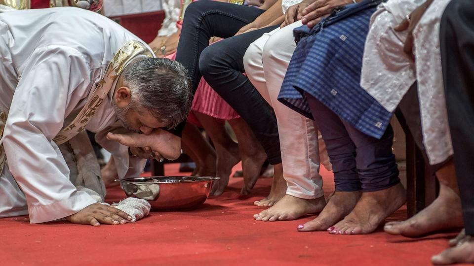 A priest kisses the feet of the 12 disciples after washing it. Jesus washed the feet of his 12 disciples before the Last Supper and thus taught them that if he, as teacher and master, could wash their feet, so also they must do to others.  (Satish Bate/HT Photo)