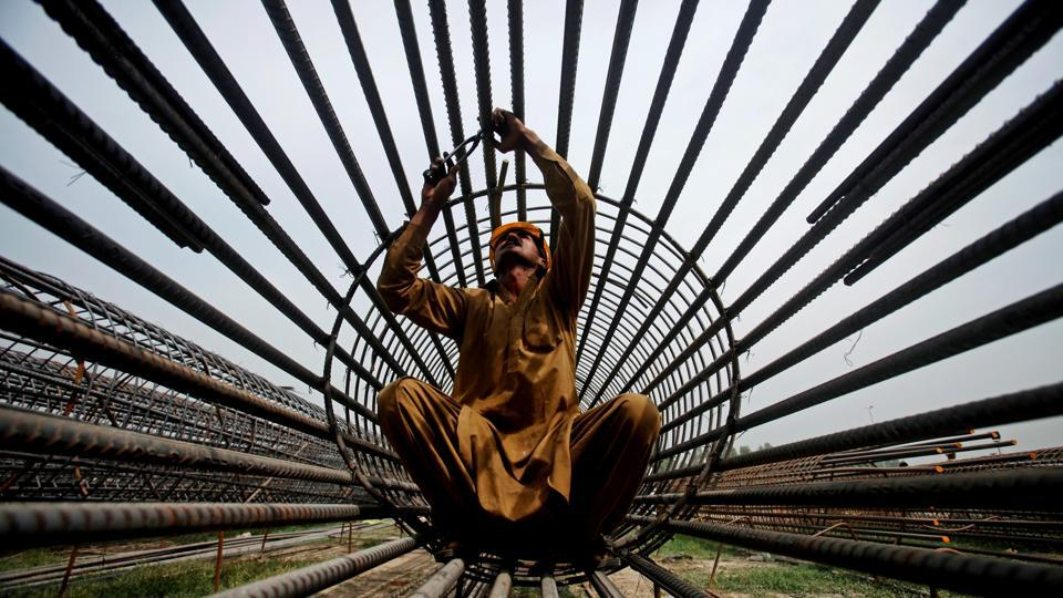 A worker ties steel bars at a construction site for a road in Peshawar, Pakistan. (Fayaz Aziz / REUTERS)