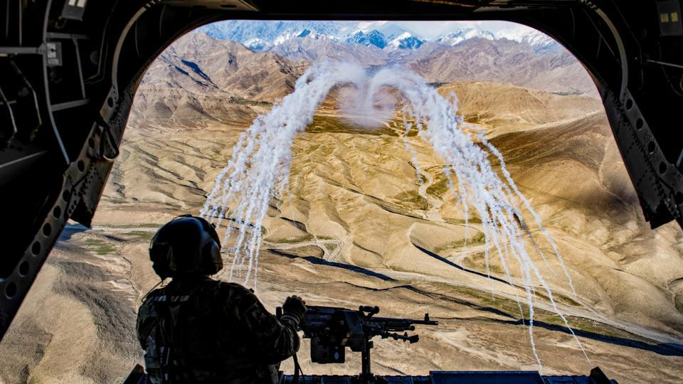 A US Army crew chief flying on board a CH-47F Chinook helicopter observes the successful test of flares during a training flight in Afghanistan. (Tech. Sgt. Gregory Brook / U.S. Air Force / REUTERS)