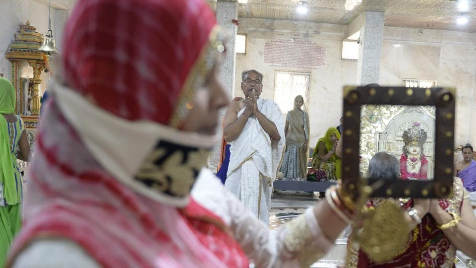 A devotee from the Jain community uses a mirror to view a statue of Lord Mahavir while offering prayers on Mahavir Jayanti at the Sri Mahavir Jain Temple in Hyderabad, Telangana. (Noah Seelam / AFP)