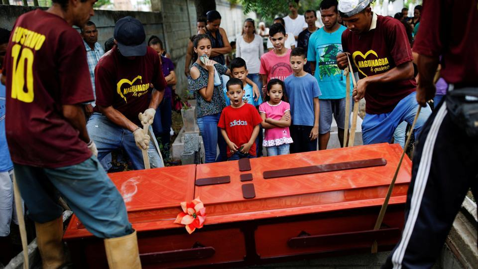 Relatives of Javier Rivas, one of the inmates who died during a riot and fire in the cells of the General Command of the Carabobo Police, react in front of his coffin during his funeral in Valencia, Venezuela. (Carlos Garcia Rawlins / REUTERS)