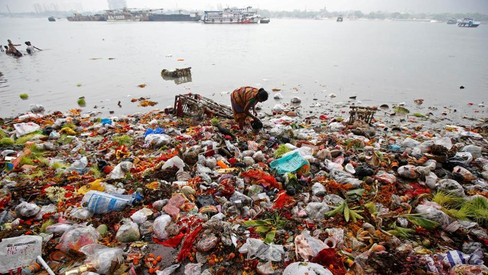 A woman collects items thrown by devotees as religious offerings in the river Ganga, after the celebrations on the final day of Navratri in Kolkata, West Bengal. (Rupak De Chowdhuri / REUTERS)