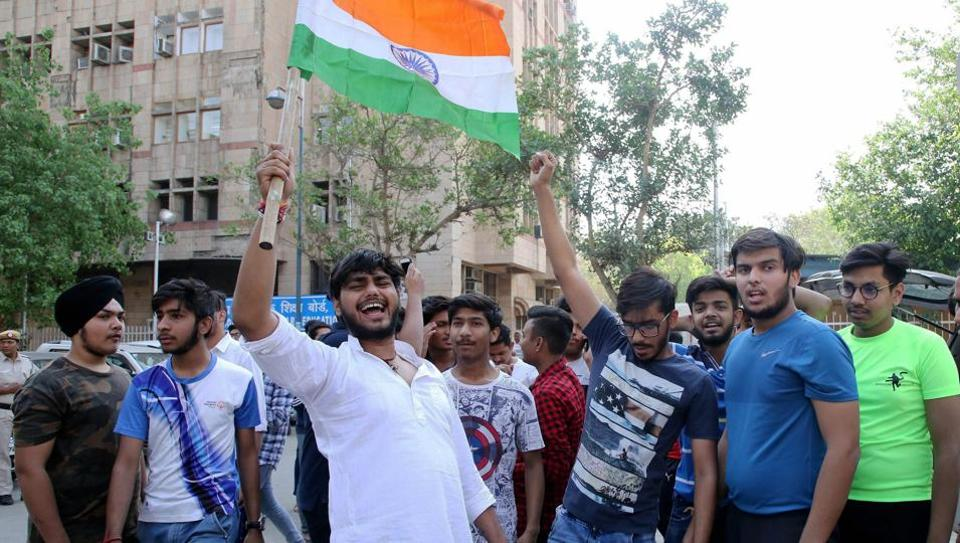 Students raise slogans in protest against the CBSE paper leak and the subsequent, in New Delhi on Friday.