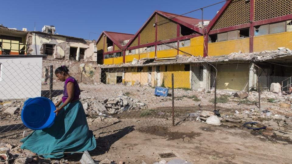 "A resident passes in front of a market destroyed in the September earthquake in Juchitan, Oaxaca State, Mexico. ""At a time when people felt so insecure and scared, they were so happy to have some form of light,"" Guerra said. ""It gave me so much satisfaction to be able to provide it."" (Yael Martinez / Bloomberg)"