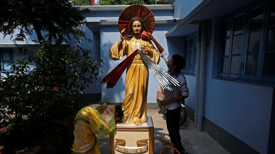 A woman prays in front of a statue of Jesus Christ as a man cleans it at a church, ahead of Good Friday celebrations, in Kolkata, India. (Rupak De Chowdhuri / REUTERS)