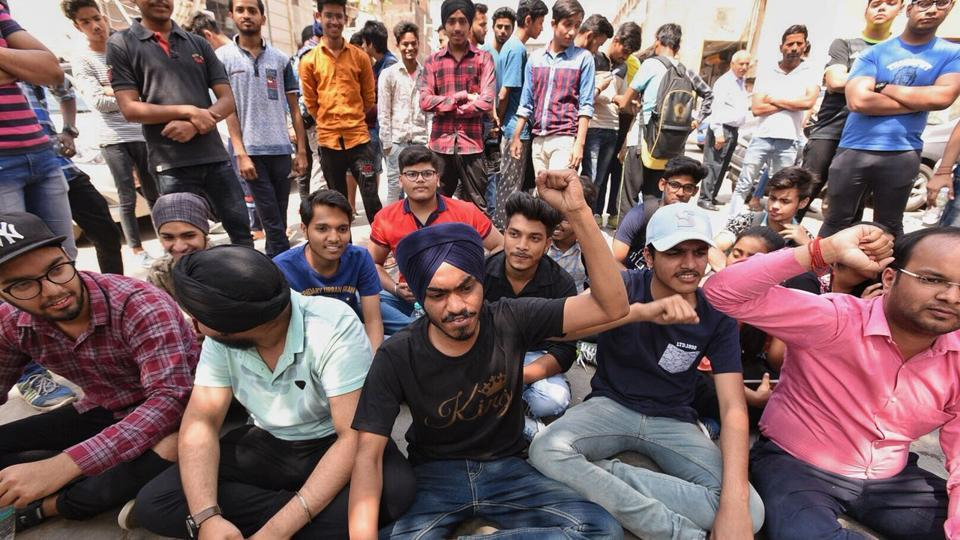 Students sit in protest outside the CBSE office in New Delhi on Saturday.