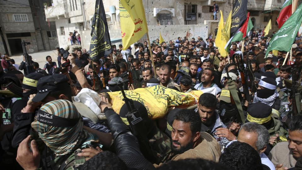 Relatives and Fateh masked militants carry the body of Hamdan Abu Amsha, 23, during his funeral in Beit Hanoun, Gaza Strip, on Saturday.