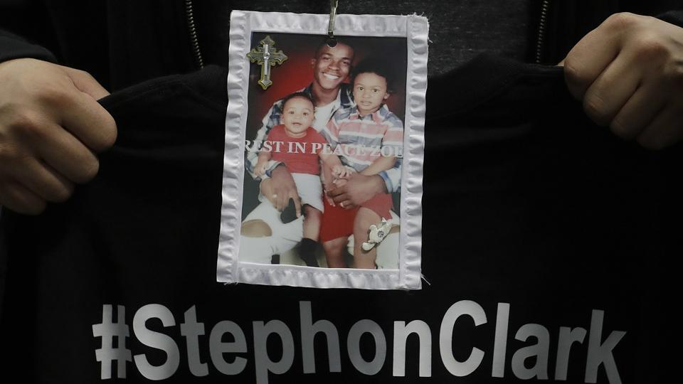 A mourner holds up a photo of police shooting victim Stephon Clark during the funeral services for Clark in Sacramento, California on March 29, 2018. Clark, who was unarmed, was shot and killed by Sacramento Police Officers, on March 18.
