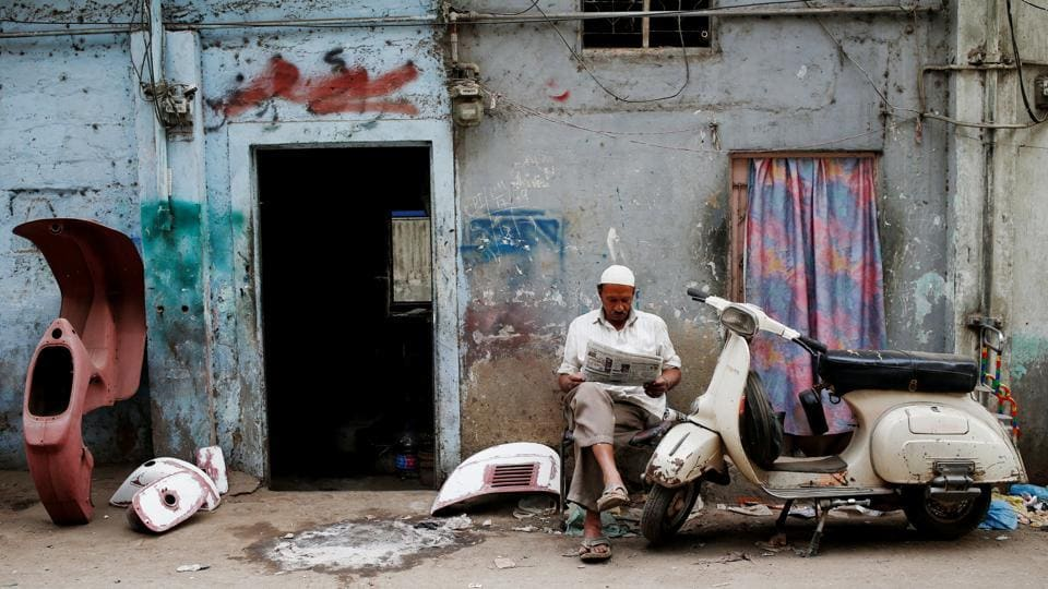 Amin, who paints repaired Vespa scooter parts, reads a newspaper outside his workshop in Karachi, Pakistan. As cheap Chinese-made motorbikes flood Pakistan's roads, fans of vintage Vespa scooters are scrambling to find spare parts and preserve models that hark back to a bygone era. (Akhtar Soomro / REUTERS)