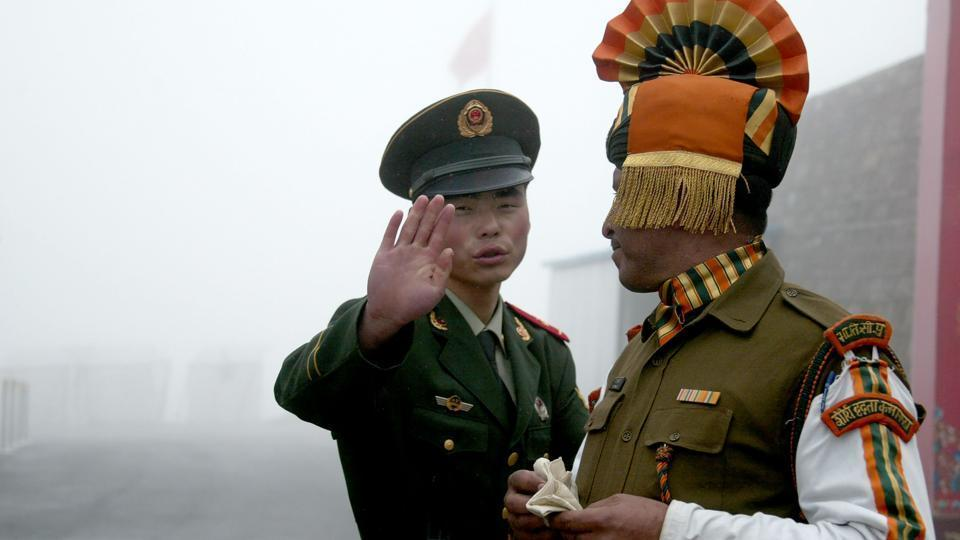 A Chinese soldier gestures to an Indian soldier at the Nathu La border crossing between India and China in Sikkim. Troops of India and China were locked in a 73-day-long standoff in Doklam from June 16 last year after the Indian side stopped the building of a road in the disputed area by the Chinese Army.